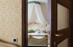 Half open door of a hotel bedroom. Half opened door of a bedroom. Hotel bedroom door half open. Hotel room welcome guests. Opening door closeup. Door handle Royalty Free Stock Images
