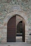 Half-open door. Half-open old door in antic, stone wall Royalty Free Stock Image