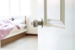 Half opened bedroom door which have someone sleeping. In the room Stock Photos
