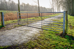 Half opened galvanized steel gate in a rural landscape Royalty Free Stock Images