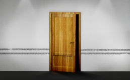 A half opened wooden door. With darkness spreading out, on a white wall Stock Images