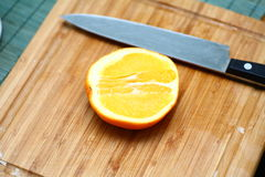 Half of orange cut with knife Royalty Free Stock Photography