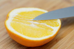 Half of orange cut with knife macro Stock Images