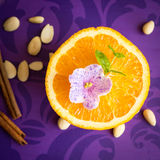 Half of orange with flower. On purple background with almonds and cinnamon. Square image Royalty Free Stock Photography