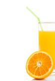 Half orange in front of glass of orange juice with straw on white background Stock Image