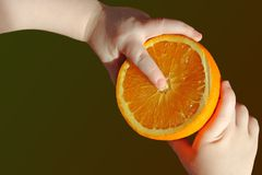 Half orange in hands of child Stock Image