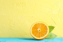 Half orange with leaves on blue table against color background. Space for text royalty free stock image