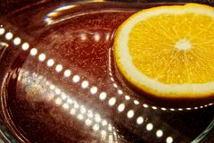 Half of the orange lies in the water next to the LEDs on. Light, orange and reflections stock photos