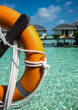 Half of orange lifebuoy in foreground on sea and bungalows backg Royalty Free Stock Photography