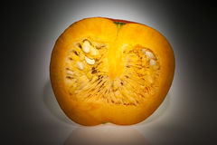An half orange pumpkin with focus lighting in dark ambiance. Single orange pumpkin with front longitudinal section after freshly harvest in autumn. We can see stock images