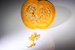 An half orange pumpkin with  seeds on the white background Stock Photo