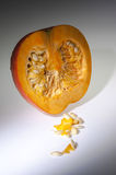 An half orange pumpkin with  seeds on the white background Royalty Free Stock Photos