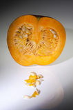 An half orange pumpkin with  seeds on the white background Stock Photos
