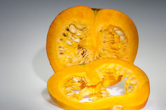 An half orange pumpkin with slice and seeds Royalty Free Stock Photography