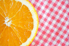 Half orange on red checkered tablecloth Stock Photography