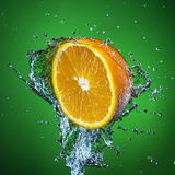 Half of orange and splash of water on green background. Half of orange and splash of water on green background Stock Photos