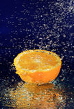 Half of orange with stopped motion water drops Royalty Free Stock Image