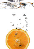 Half orange in water. Orange water splash forming water bubbles royalty free stock photos
