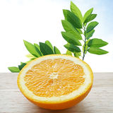 Half orange on wooden table, with green leave in background Stock Photo