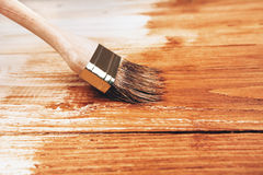 Half painted wooden boards. Varnishing a wooden shelf using paintbrush Royalty Free Stock Photo