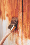 Half painted wooden boards. Varnishing a wooden shelf using paintbrush Stock Image