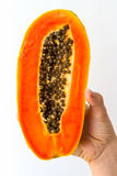 Half Papaya in Hand. A half ripe papaya with seeds, held in the hand of a young woman, isolated on white Royalty Free Stock Photo