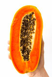 Half Papaya. A half ripe papaya with seeds, held in the hand of a young woman, isolated on white Stock Photos