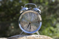 Half past seven. One alarm clock on a rock Stock Image