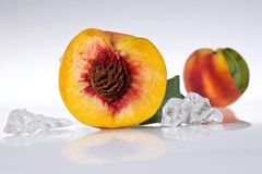 Half peach. And crushed ice cubes Stock Photo