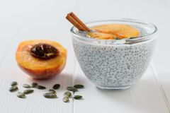 Half peach, cinnamon stick, pumpkin seeds and Chia seed pudding on wooden table. stock photos
