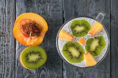 Half peach, half kiwi and Chia seed pudding on a dark wooden table. The view from the top. Flat lay. stock images