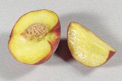 Half peach beside a slice on gray and rough surface Royalty Free Stock Photo