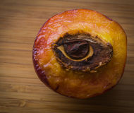 Half of peach with stone in shape of an eye Stock Image