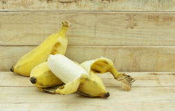 Half peeled Asian yellow banana on wood background. Royalty Free Stock Images