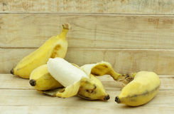 Half peeled Asian yellow banana on wood background. Stock Image