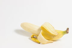 Half peeled banana isolated on a white background. Half peeled banana isolated on a white background with copy space Stock Photo