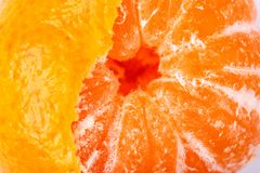 Half peeled mandarin. Half peeled mandarin close up on a white background. Mandarin with peel stock image