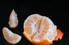 Half peeled tangerine with rind and two slices Royalty Free Stock Image