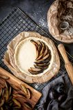Half of the pie with cut ripe plum fruits. View from the top. stock photography