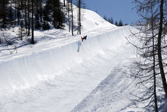 Half pipe trail. An half pipe trail with a snowboarder. He does a trick - at Valmalenco - Italy Stock Photography