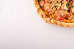 Half pizza on white wooden background copy space top view. Close up stock photography