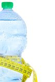 Half plastic bottle with water, drops and measuring tape, concept of fitness and diet Royalty Free Stock Images