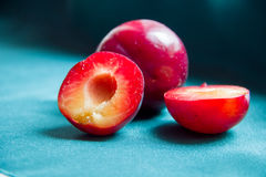 Half plums on a background of whole plums on the green fabric. Royalty Free Stock Photography