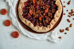 A half of plums pie with dried apricots on dark plate decorated with brown raisins on light table with white cloth Stock Photography