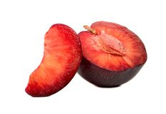 Half plums with slice. Half of a juicy red plum with slice on white background Royalty Free Stock Photo
