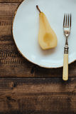 Half a Poached Pear on White Plate with Vintage Fork on Rustic Table Stock Photos