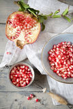 Half pomegranate with branch and grains on bowl on wooden rustic table with vintage strainer full of grains Fotografia de Stock Royalty Free