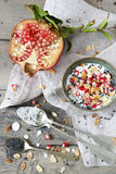Half pomegranate and little portion of natural white yogurt with grains, seed and almond slices Royalty Free Stock Photo