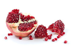 Half of pomegranate, piece and some berries. Isolated on the white background Stock Images