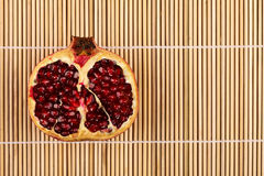 Half pomegranate on wooden sticks Royalty Free Stock Photos